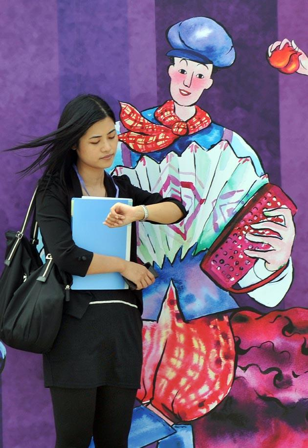A media representative checks her watch in front of a billboard advertising the upcoming Hong Kong Wine and Dine Festival in Hong Kong on October 27, 2011. AFP PHOTO.