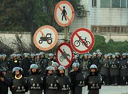 Police block villagers after a large crowd formed at the scene of environmental protests over the past few days in the town of Haimen, Guangdong Province on December 22, 2011. AFP PHOTO