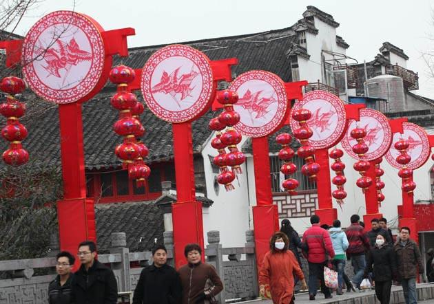 Tourists walk by festival decorations at the Confucius Temple in Nanjing, capital of east China's Jiangsu Province, 16 Jan, 2012. Xinhua Photo