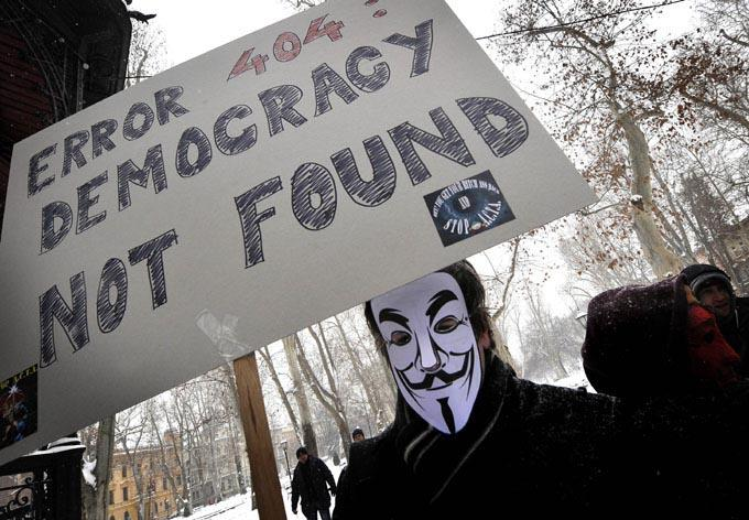 A protester wearing an Anonymous Guy Fawkes mask and holding a placard, took part in a demonstration against controversial Anti-Counterfeiting Trade Agreement (ACTA) as part of an international day of action against the increasingly-contested accord, in Zagreb on February 11, 2012.  AFP Photo