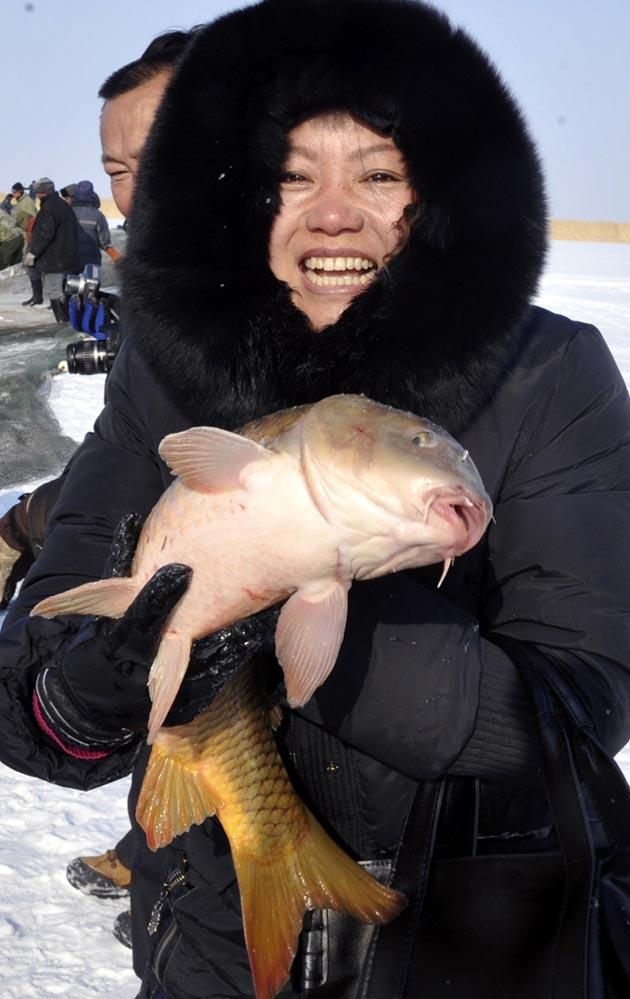 A tourist held a big carp caught from the iced lake in Fuhai County, northwest China's Xinjiang Uygur Autonomous Region, Jan 14, 2012. Xinhua Photo