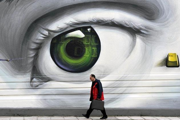 A man walks by a wall adorned with graffiti in Athens on 8 March 2012. AFP Photo