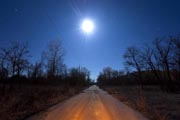 A deserted road leading into the toxic town of Picher glows beneath a full moon in Picher, Oklahoma, USA, 6 February 2012. EPA Photo
