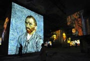 """People looked at an audio visual show projecting on the walls of the """"Quarries of lights"""" paintings of French Post-Impressionist artist Paul Gauguin and Dutch post-Impressionist painter Vincent van Gogh, on 20 March, 2012, in a French city. AFP Photo"""
