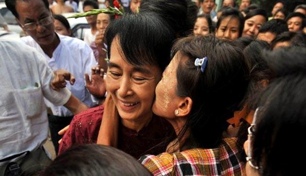 Myanmar democracy icon Aung San Suu Kyi (centre) is kissed by a supporter during a visit to the country's ancient temple city of Bagan on July 7, 2011. AFP Photo