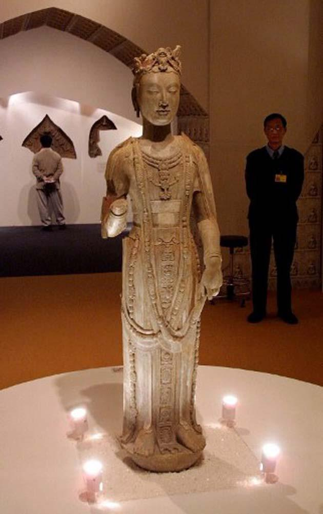 A security guard kept a watchful eye on a standing stone image of a Bodhisattva from Northern Qi, (circa 550-770 AD) at a Buddhist Sculptures exhibition at the Hong Kong Museum of Art, Tsim Sha Tsui, in 2001.  (AFP Photo)