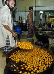 A Pakistani sweet maker prepared gulab jamun at a shop in Karachi. (AFP Photo)