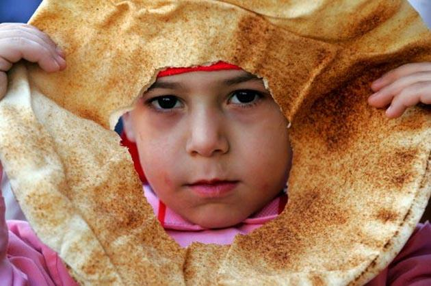 A Palestinian boy looked through a perforated piece of pita bread. (AFP Photo)