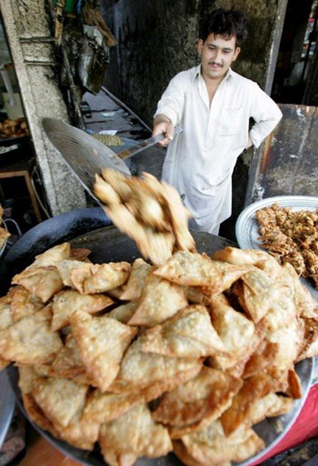 A Pakistani vendor dropped samosas into a basket.   (AFP Photo)