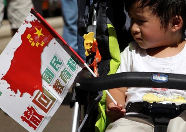 "In a photograph taken on July 29, 2012, a child carried a flag reading ""please withdraw national education"" as demonstrators marched during a protest against the government's efforts to implement national education in Hong Kong. AFP Photo"