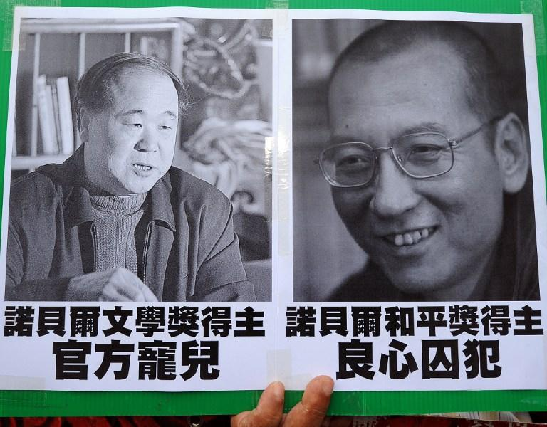 A protester held pictures of Chinese writer Mo Yan (left) and Chinese dissident Liu Xiaobo (right) during a demonstration in front of the Chinese liaison offices in Hong Kong on October 13, 2012. AFP Photo