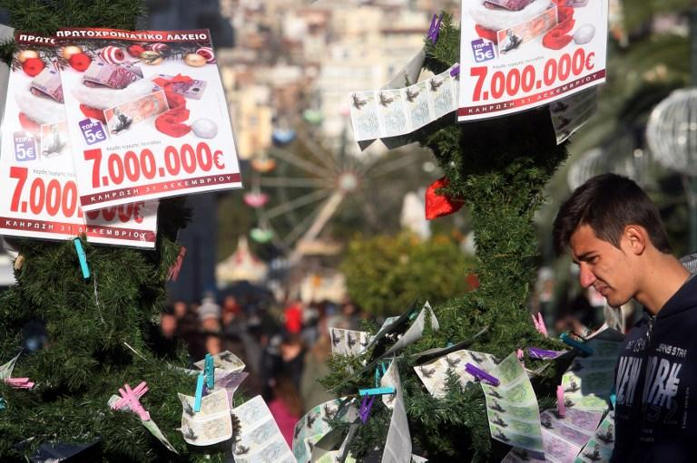 A man looked at the New Year's lottery tickets and ads hanging from a Christmas tree in Greece on December 13, 2012. AFP Photo