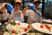 Employees served mozzarella cheese at a counter of the Eataly food emporium on June 12, 2012 in Rome. AFP Photo