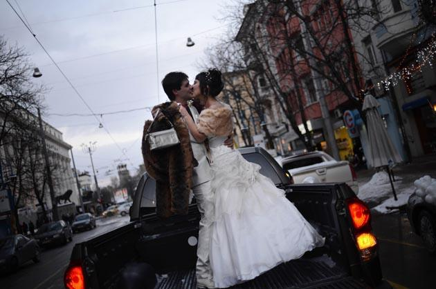 "A Bulgarian couple kissed on the back of a pick-up truck before their wedding ceremony in Sofia on December 12, 2012. More than a hundred couples in Bulgaria chose to mark the once in a lifetime date 12/12/12 by saying ""I do"" on the special day. AFP Photo"