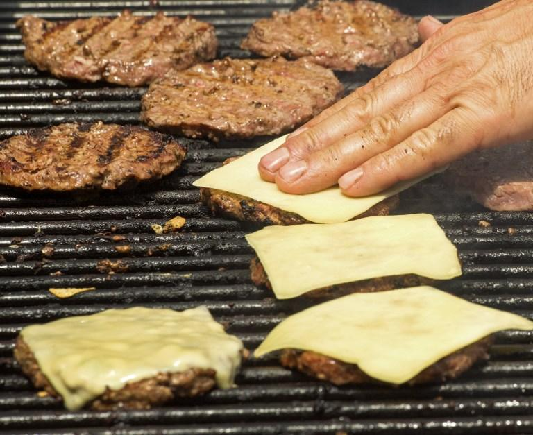 Hamburgers that were 100 percent grass-fed beef from a certified organic herd and topped with 100 percent grass-fed raw cheese were grilled by a street vendor for sale at seven USD each on July 12, 2012, in Washington, DC. AFP Photo
