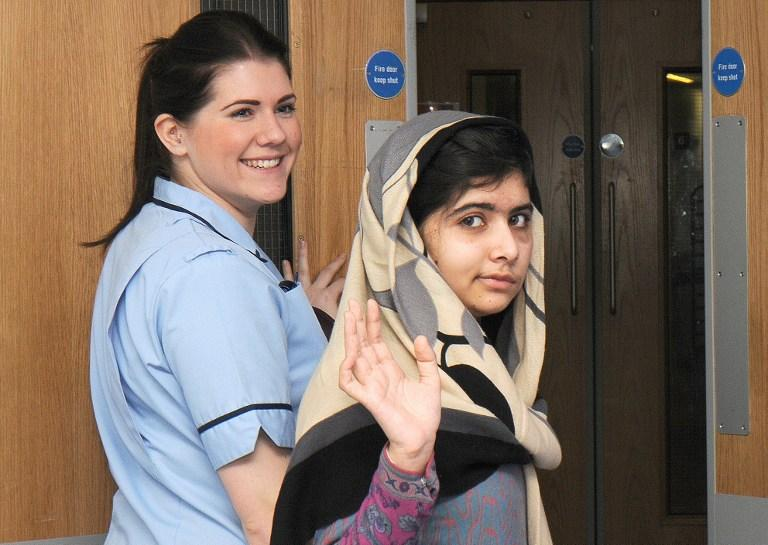 A handout picture received on January 4, 2013 from the Queen Elizabeth Hospital in Birmingham and taken on January 3, 2013 shows injured 15 year-old Pakistani schoolgirl Malala (right) waving as she is discharged from the Queen Elizabeth Hospital in Birmingham in central England. AFP Photo/ Queen Elizabeth Hospital.