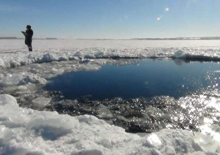 A handout photo taken on February 15, 2013, and provided by Chelyabinsk region police department shows a police officer standing near a six-metre (20-foot) hole in the ice of a frozen lake, reportedly the site of a meteor fall, outside the town of Chebakul in the Chelyabinsk region. AFP Photo/ Chelyabinsk Region Police Department