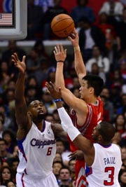 Jeremy Lin of the Houston Rockets (centre) shoot against DeAndre Jordan (left) and Chris Paul (right) of the LA Clippers during their NBA game in Los Angeles, California on February 13, 2013. AFP Photo