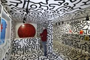 This picture taken on April 17, 2013 shows a spectator looking at 'Outdoor Painting', as he stands in the 'Tokyo Pop Shop (Container)', both art creations by US artist Keith Haring. AFP Photo