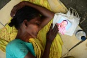 A Bangladeshi woman slept as she held the portrait of her missing relative. AFP Photo