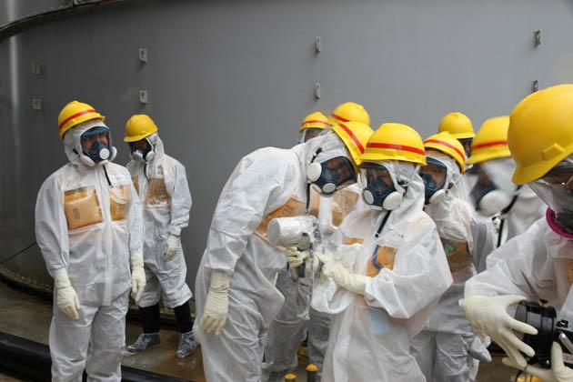 This handout picture taken by Japan's Nuclear Regulation Authority on August 23, 2013 shows nuclear watchdog members including Nuclear Regulation Authority members in radiation protection suits inspecting contaminated water tanks at the Tokyo Electric Power Co (TEPCO) Fukushima Dai-ichi nuclear power plant in the town of Okuma, Fukushima prefecture. (AFP Photo/Nuclear Regulation Authority)