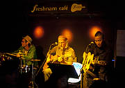 Nam (right) performed with a Canadian guitar player and a French drummer at Freshnam Cafe in Lijiang, southwest China's Yunnan Province, on Nov 8, 2013. (Xinhua Photo)