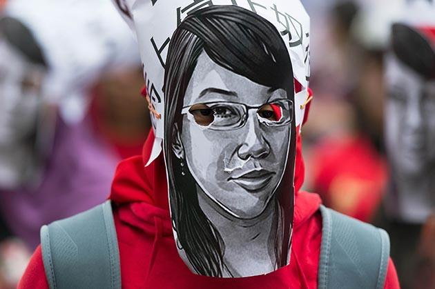 A migrant worker wore a mask resembling a likeness of former Indonesian maid Erwiana during a Labour Day rally in Hong Kong on May 1, 2014.  (AFP Photo)
