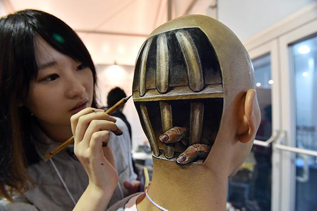 """A body painting of fingers sticking out from cell bars on the head of Ryonosuke Tanaka, painted by Japanese body-painting artist Hikaru Cho during """"Tokyo Designers Week"""" in Tokyo (AFP Photo)"""