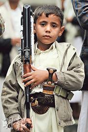 也門一名男童上周五攜槍在薩那參加反沙特空襲示威。(法新社)