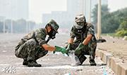 解放軍防化部隊的士兵,在天津濱海新區爆炸點附近,搜集白色晶體樣本。(新華社)