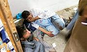 無國界醫生的阿富汗醫護職員在空襲中受傷,一名挨在牆邊的傷者穿著無國界醫生的服裝。(法新社)