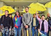 被告曾健超(前左三)昨離庭時仍下着雨,他穿上灰色西裝,衣領上繫上黃絲帶心口針,在立法會議員梁國雄(前左二)及一眾撐起黃傘的支持者陪同下到庭,他們散庭後在庭外高叫「和平示威無罪,公民抗命無罪」口號。(鄧宗弘攝)