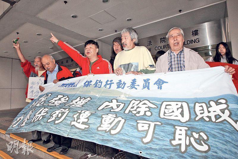 古思堯(左一)等在庭外舉起「只有抗爭才是硬道理,我故意焚燒侮辱國旗區旗」的標語,他又飲酒預祝自己將第5次入獄。(李紹昌攝)