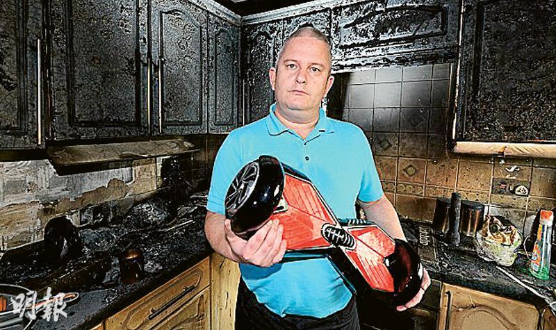 英國肯特郡一名男子今年11月買了電動平衡車給3名孫兒,不料其中一部突然爆炸,令全家付諸一炬,圖為他手執電動平衡車,在被燒毁的廚房留影。(網上圖片)