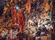 搜索工作入黑後繼續,搜索犬奉召到場,在瓦礫中尋找被困者。 (新華社)