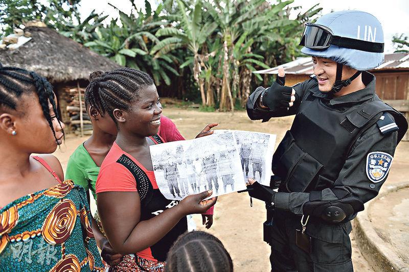 聯合國各國維和預算分攤比例即將揭曉,中國將躍居第二。圖為11月初,在利比里亞格林維爾一個村莊,中國維和警察防暴隊隊員與當地村民交流。(新華社)