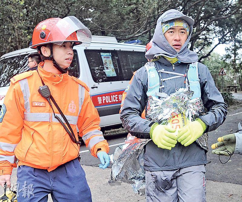 大帽山封閉上山道路期間,陸續有越野長跑參賽者因低溫症不適,披着保暖氈由救護員帶到山腳接受治療。(衛永康攝)