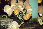 消防員入夜後在靴底加上冰爪,方便在結冰路面行走。(林俊源攝)