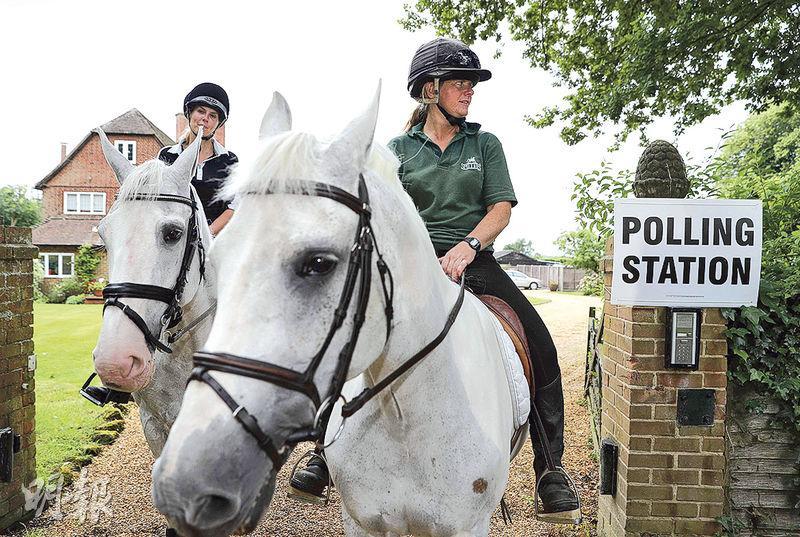 在倫敦西部的雷丁,昨日有騎馬民眾經過私人住宅改成的票站。(法新社)