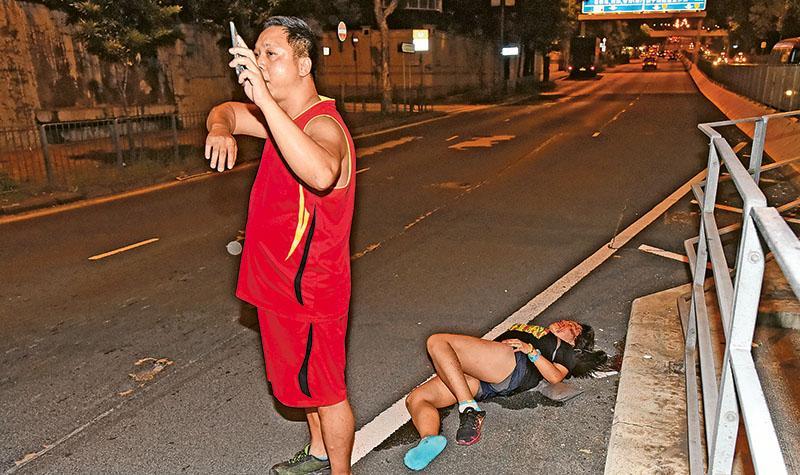 18歲浸大二年級劉姓女學生(臥地者)昨凌晨疑戴耳機跑步,遭一輛貨車撞倒。肇事司機(左)事後以手機照明,向路過的司機示意發生了車禍。