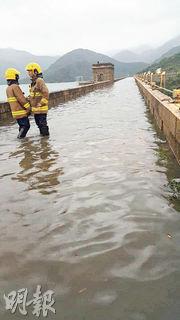 黑雨下,原本行車的大潭水塘道水壩變成河道,消防員要在場戒備及勸阻市民勿通過橋面,免生危險。(網上圖片)