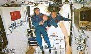 北京航天飛行控制中心的屏幕畫面顯示,太空人景海鵬(左)伸手扶住飄浮進入天宮二號實驗艙的陳冬。(新華社)