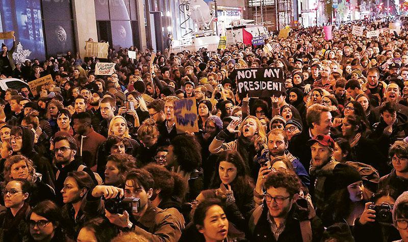 周三在紐約市的特朗普大樓外有大批示威者聚集,有人舉起「不是我的總統」標語牌抗議特朗普當選。(法新社)