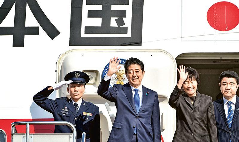 安倍(左二)與妻子(左三)昨由東京羽田機場出發,前往美國與總統當選人特朗普會面。兩人登機前向在場人員揮手。(法新社)