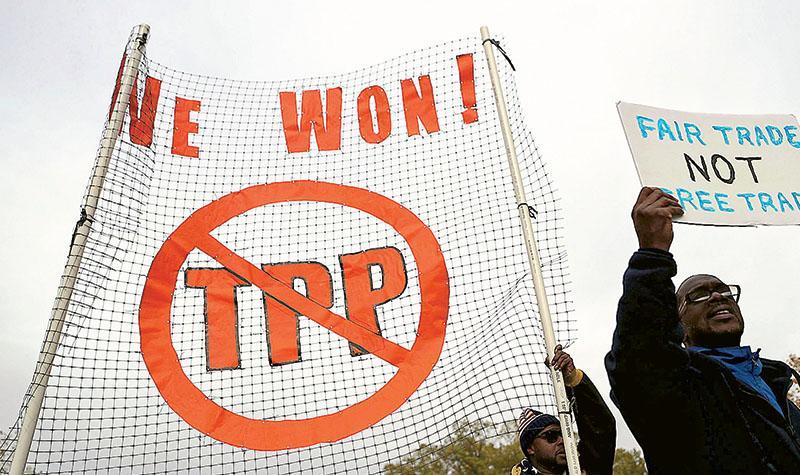 上周一在美國首都華盛頓有民眾集會反對TPP,示威者舉起「要公平貿易,不是自由貿易」標語。(法新社)