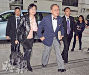 曾蔭權(右)與妻子鮑笑薇(左)於開庭前個多小時乘坐私家車抵達高等法院,他向記者說「早晨」後偕同其妻手牽手步入法院。(劉焌陶攝)