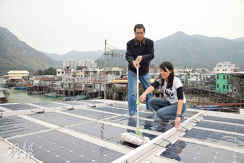 梁先生(左)的棚屋屋頂安裝了太陽能板,並連接電網,基本上毋須維修,只要不時清除太陽能板表面的灰塵,便能源源不絕發電。右為世界自然基金會香港分會氣候及公眾參與主任杜珮煒。(世界自然基金會香港分會提供)
