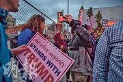 特朗普的支持者(左)周日在奧斯卡頒獎禮會場附近,與一名路過的婦人爭拗起來。(法新社)