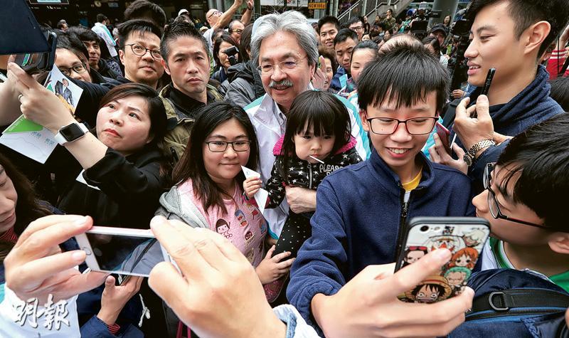 特首候選人曾俊華(後中)昨午到大圍與市民接觸,吸引大批市民圍觀,市民爭相上前與曾俊華握手、自拍,曾更抱起小孩合照。(李紹昌攝)
