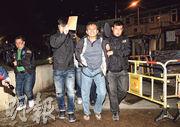 昨凌晨3時許,探員將涉嫌兇殺被捕疑犯(中)鎖上手鐐及腰纏鐵鏈押走,疑犯拒絕戴上頭套,不斷大叫「警察無證據拉我」,探員用文件替其遮面部。(蔡方山攝)